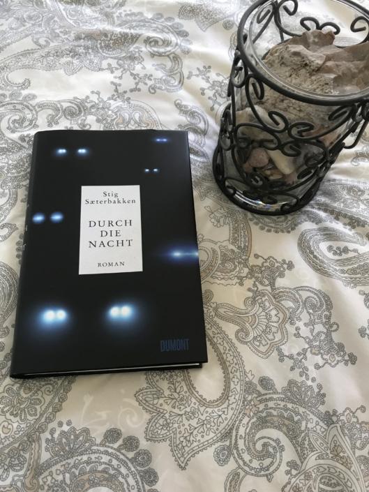Deutsche Ausgabe von »Durch die Nacht« auf einer Decke liegend