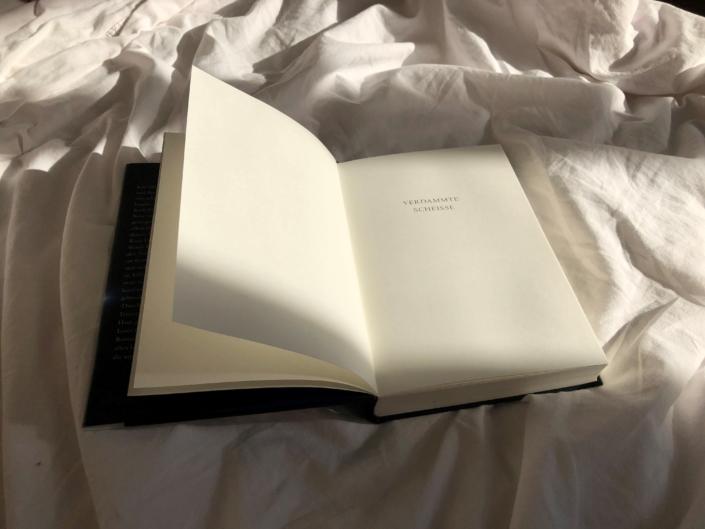 Aufgeschlagenes Buch auf einer Decke liegend