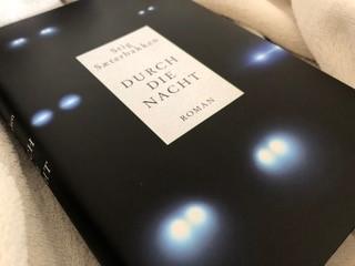 Ein Exemplar von »Durch die Nacht« auf einer hellen Decke liegend