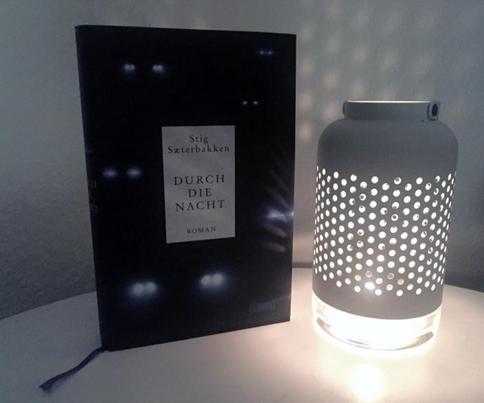 Deutsche Ausgabe von »Durch die Nacht« neben einer Lampe stehend