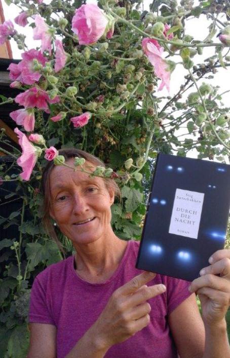 Leserin mit deutscher Ausgabe von »Durch die Nacht« unter Blumenranken stehend
